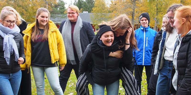 En skrattande medlem bär en annan medlem på ryggen. Ett tiotal glada medlemmar står runtomkring och kollar på.